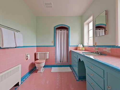 um banheiro feminino com cerâmica rosa no piso e parede