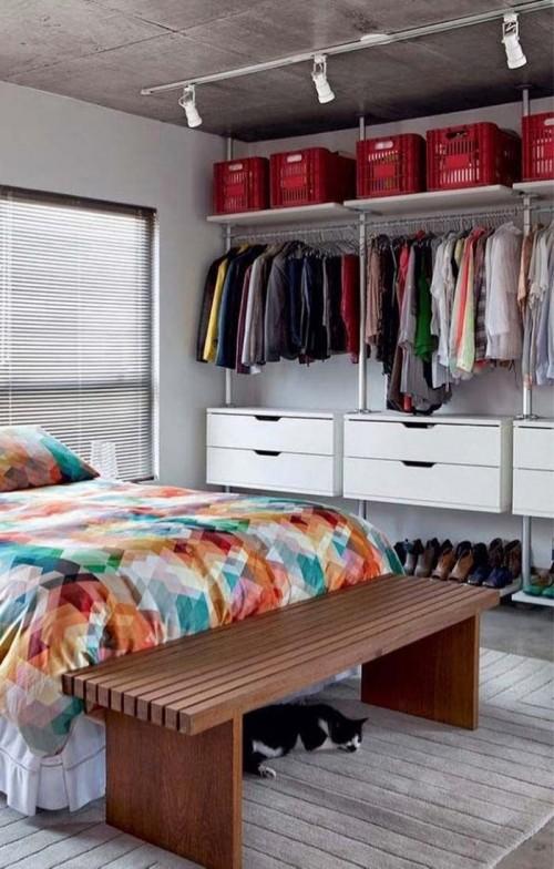 Gavetas brancas com banco marrom dentro do closet aberto